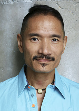 Alan Tse wearing a bright blue shirt, with a cement wall background