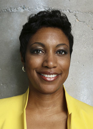 Rosemary Ugboajah smiling, wearing a yellow blazer, against a concrete wall