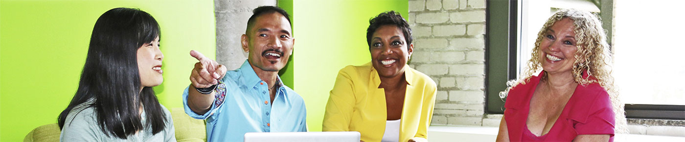The Neka Creative team engaged in conversation in the office, with big smiles all around.