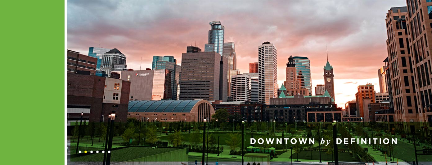 "Minneapolis skyline at dusk, with ""Downtown by Definition"" overlayed"