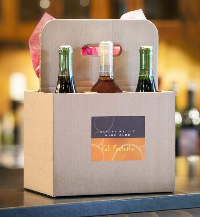 Six bottles of wine in a cardboard holdster, with the brown and orange wine club logo